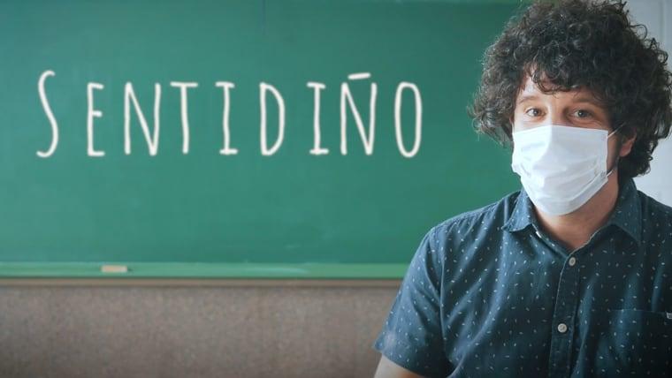 O actor Xosé Antonio Touriñán con máscara diante dun encerado no que está escrita a palabra Sentidiño, nun plano dun anuncio